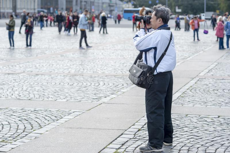 Man tourist Asian appearance photographs on camera attractions on the Palace square of St. Petersburg, Russia, September 2018. stock photo