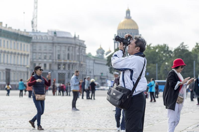 Man tourist Asian appearance photographs on camera attractions on the Palace square of St. Petersburg, Russia, September 2018. stock images