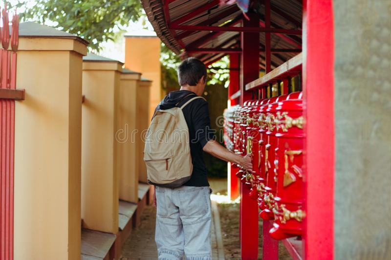 Man tourist with backpack turns the prayer drum, man tourist back to the camera stock photos