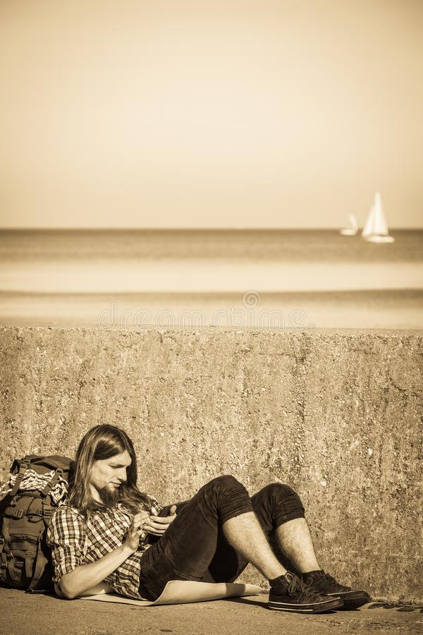 Man tourist backpacker sitting with tablet outdoor. Man tourist backpacker relaxing outdoor sitting by grunge wall using tablet. Internet, tourism active royalty free stock photos