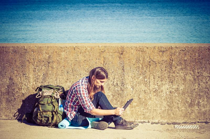 Man tourist backpacker sitting with tablet outdoor. Man tourist backpacker relaxing outdoor sitting by grunge wall using tablet. Internet, tourism active royalty free stock photo