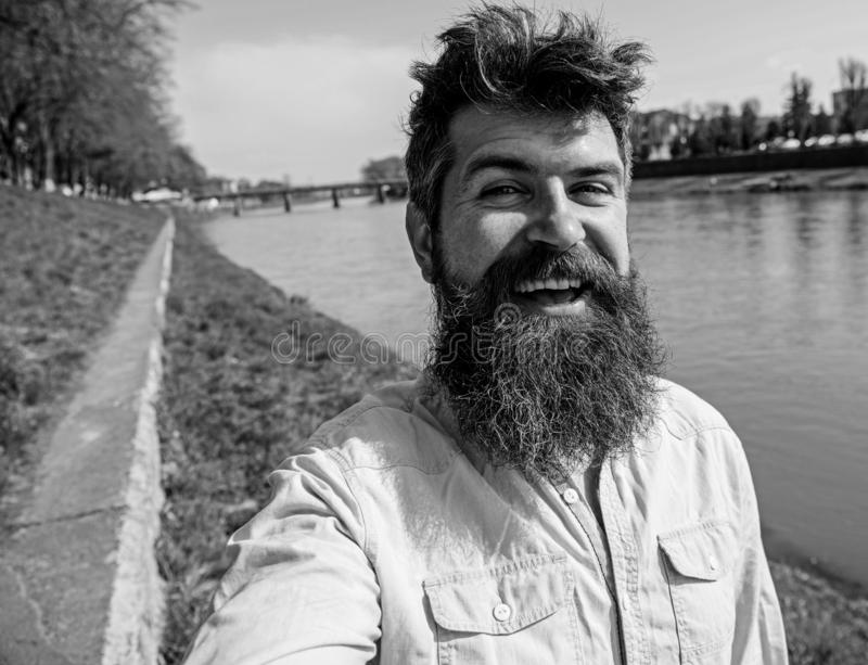 Man, tourist with beard and mustache on cheerful, smiling face, riverside background. Selfie photo concept. Hipster stock image