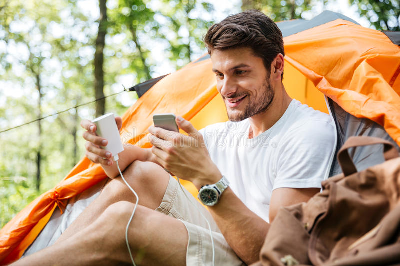 Man tourist charging battery of mobile phone in touristic tent. Cheerful young man tourist sitting and charging battery of mobile phone in touristic tent royalty free stock images