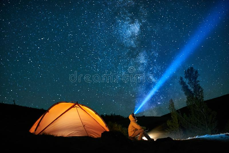 Man tourist with flashlight near his camp tent at night. royalty free stock photography