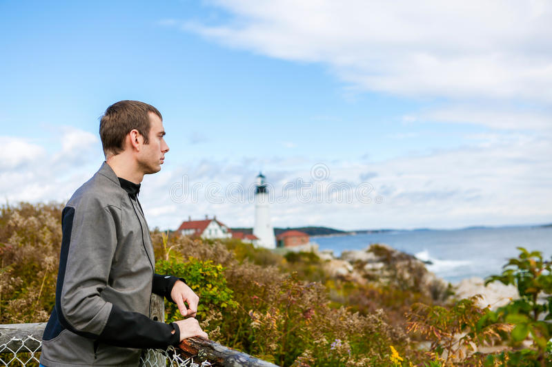 Man tourist looking away. At the background the Portland Headlight Lighthouse. In South Portland Maine stock images
