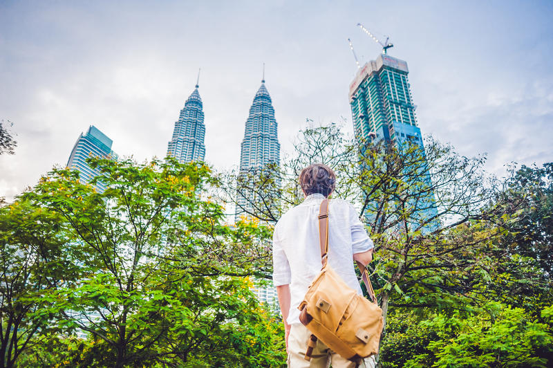 Man tourist in Malaysia looks at the Petronas Twin Towers stock photography