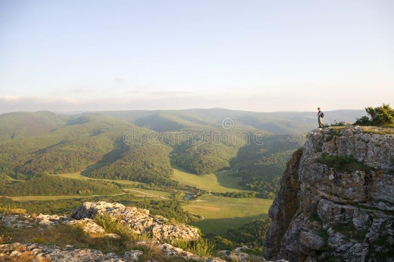 Man tourist on peak of mountain. royalty free stock photography