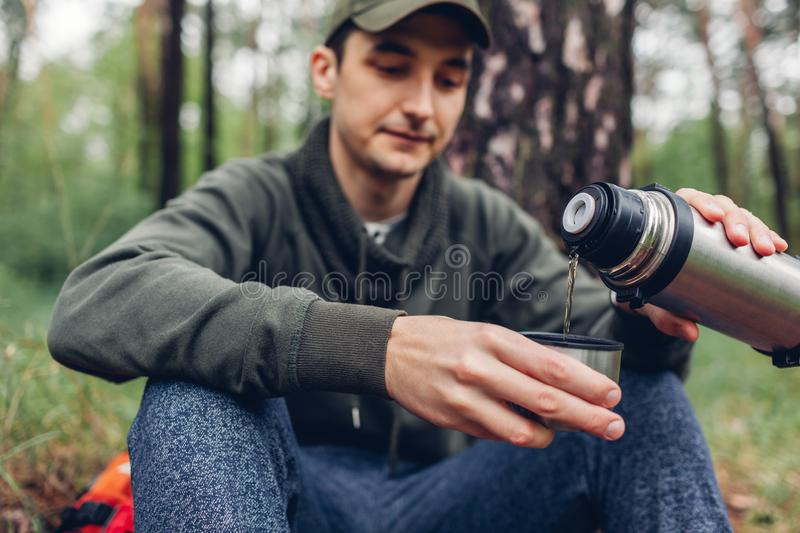 Man tourist pours hot tea out of thermos in spring forest. Camping, traveling and sport concept royalty free stock images