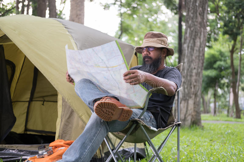 Man tourist sitting on chair and reading map in front of tent at. Camping site in forest. Outdoor activity in summer. Adventure traveling in national park royalty free stock image