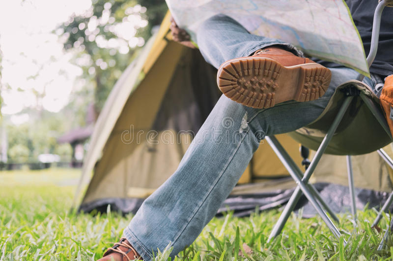 Man tourist sitting on chair and reading map in front of tent at. Camping site in forest. Outdoor activity in summer. Adventure traveling in national park stock photography