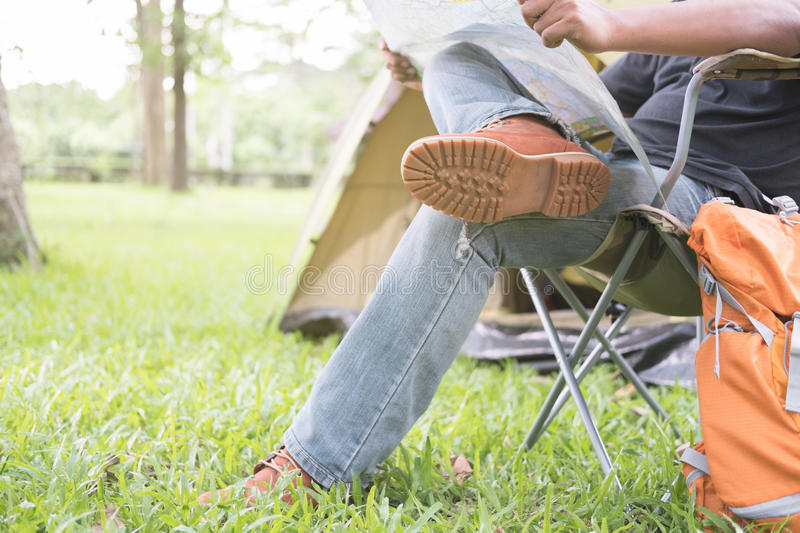 Man tourist sitting on chair and reading map in front of tent at. Camping site in forest. Outdoor activity in summer. Adventure traveling in national park stock photo