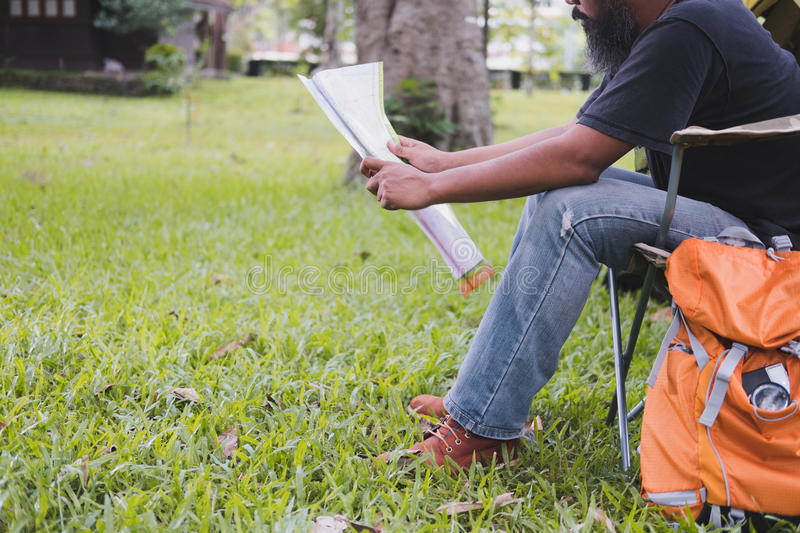 Man tourist sitting on chair and reading map in front of tent at. Camping site in forest. Outdoor activity in summer. Adventure traveling in national park stock images