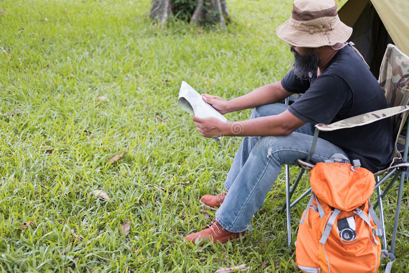 Man tourist sitting on chair and reading map in front of tent at. Camping site in forest. Outdoor activity in summer. Adventure traveling in national park royalty free stock photo