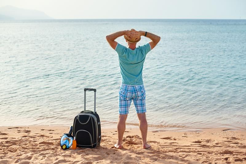 Man tourist in summer clothes with a suitcase in his hand, looking at the sea on the beach, concept of time to travel royalty free stock photos