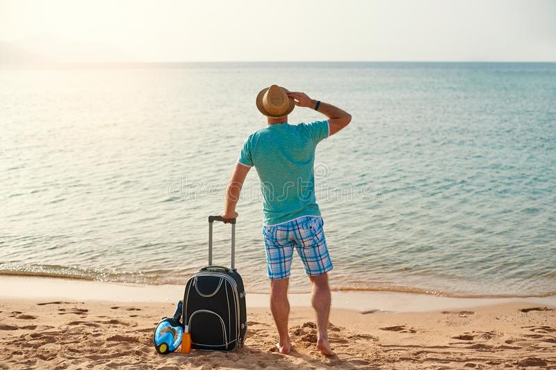 Man tourist in summer clothes with a suitcase in his hand, looking at the sea on the beach, concept of time to travel.  stock photography