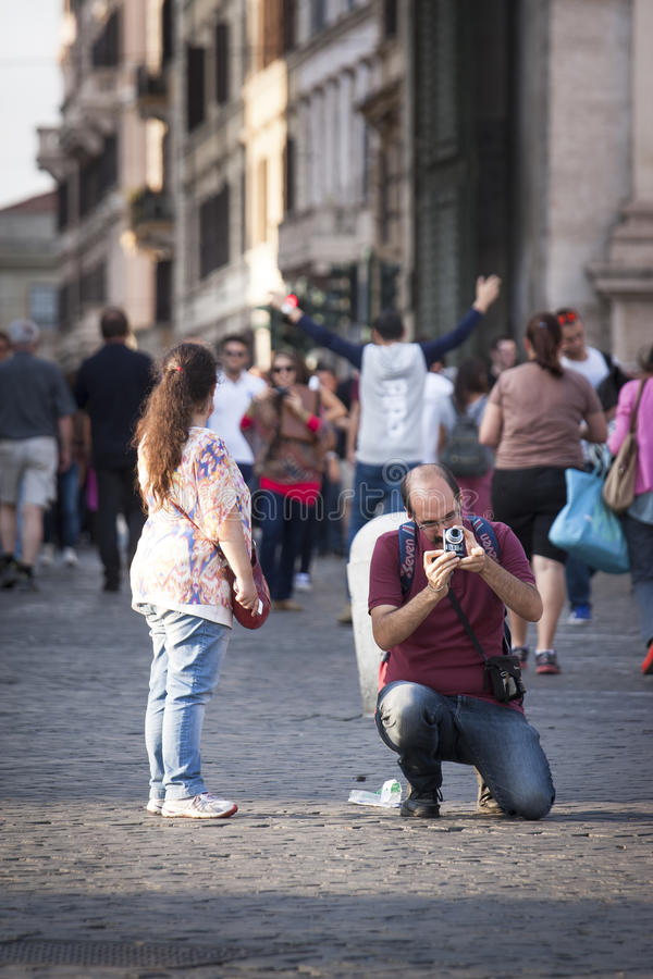 Man tourist taking a picture, girl looking. A lot of tourists. royalty free stock image
