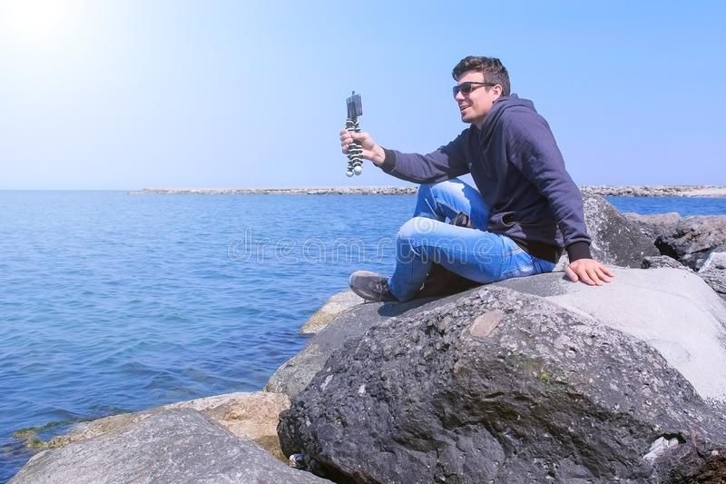 Man tourist talk smartphone video chat at sea with small tripod sits on stone. stock photography