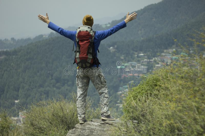 Man tourist trekking with backpack in valley mountains success happy stock images