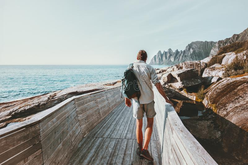 Man tourist walking on beach wooden bridge with backpack stock image