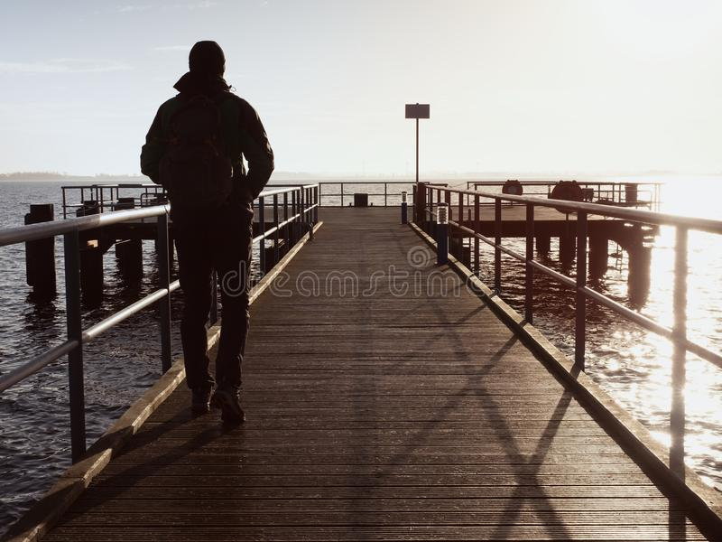 Man tourist at wooden sea pier. Cold windless morning with gradient sunlight. Smooth water. Level in bay royalty free stock photography
