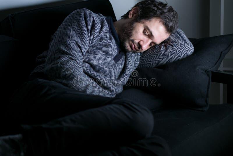 Man trött och deprimerat ligga på soffan royaltyfri bild