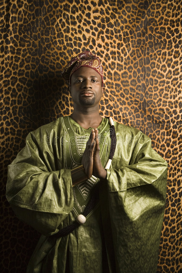 Man in traditional African clothing. Portrait of African- American mid-adult man in prayer wearing traditional African clothing royalty free stock images