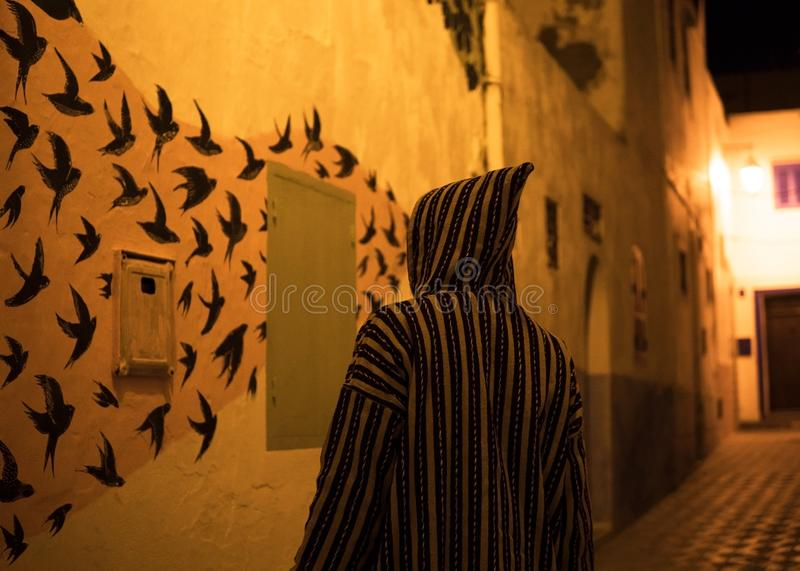 Man in Traditional moroccan djellaba Looking at street art while walking on the street of Asilah Medina, on Atlantic stock photos
