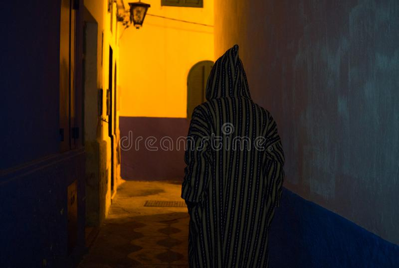 Man in Traditional moroccan djellaba walking on the street of Asilah Medina, on Atlantic Coast in Morocco stock photography