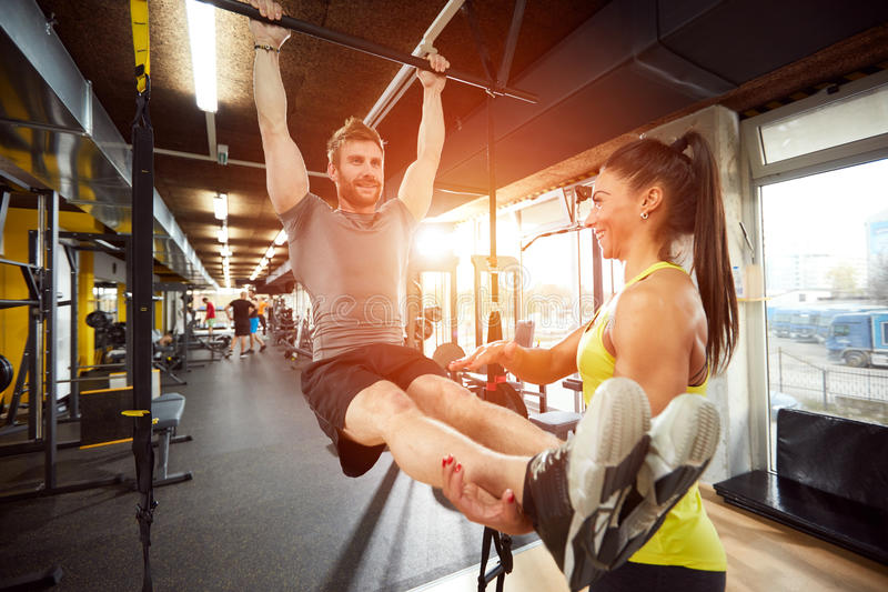 Man with trainer in gym on exercise equipment royalty free stock image