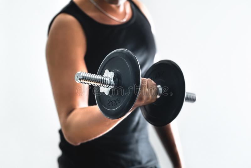 Man training arms and doing bicep curls with dumbbell. Guy working out. Person training muscles. Workout, fitness and bodybuilding concept. White background royalty free stock photography