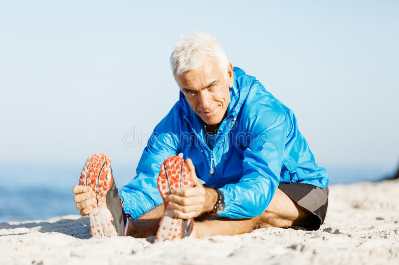 Man training on beach outside. Handsome caucasian male doing exercises on beach royalty free stock images