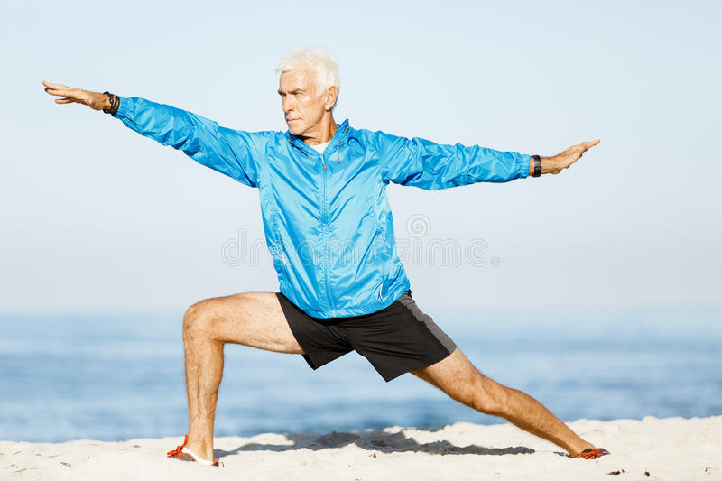 Man training on beach outside. Handsome caucasian male doing exercises on beach stock images