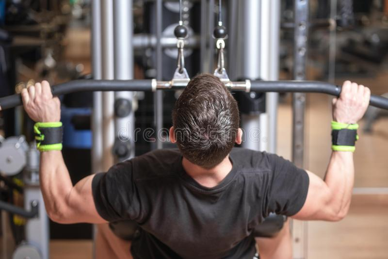 Man training dorsal muscles by taking handles and bringing them down. Strength exercising concept. stock image