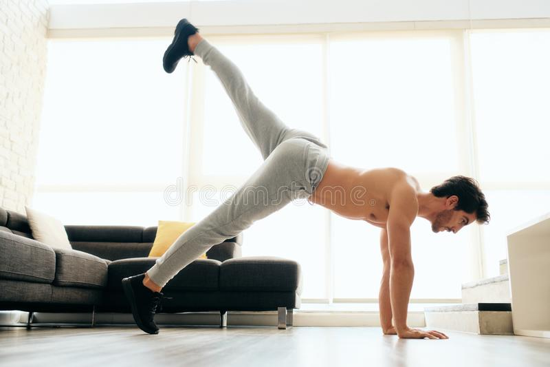 Man Training Legs and Back Muscles Doing Plank with Leg Lift. Fit young white man training at home. Handsome hispanic male athlete working out for wellbeing in stock images