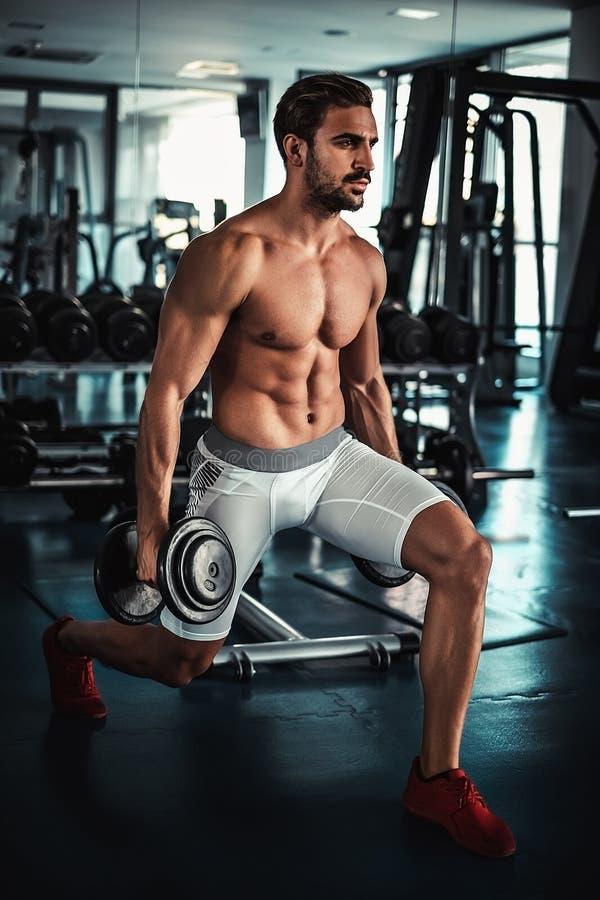 Man training legs in the gym. Shirtless man training legs in the gym royalty free stock photography