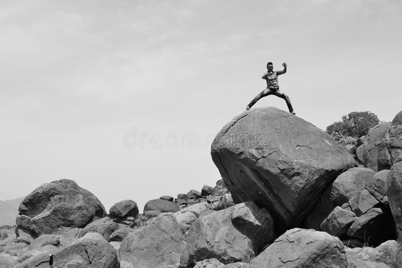 Man training on martial arts on a pile of rocks in the desert -B&W-. Man fighting on a pile of rocks all alone in the desert stock images