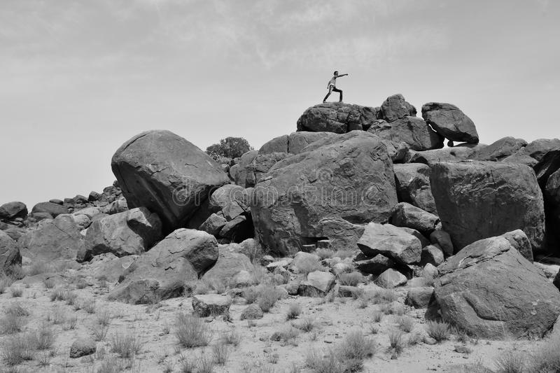 Man training on martial arts on a pile of rocks in the desert #2 -B&W-. Man fighting on a pile of rocks all alone in the desert royalty free stock photos
