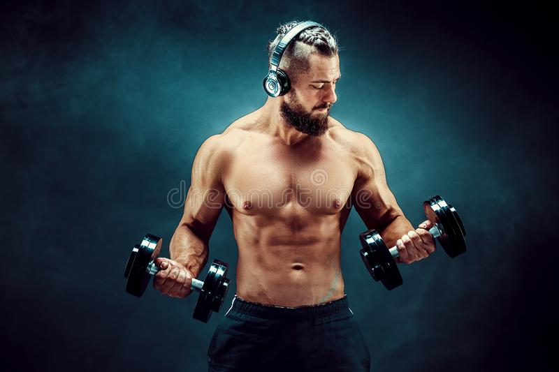 Man training muscles with dumbbells in studio on dark background. royalty free stock images