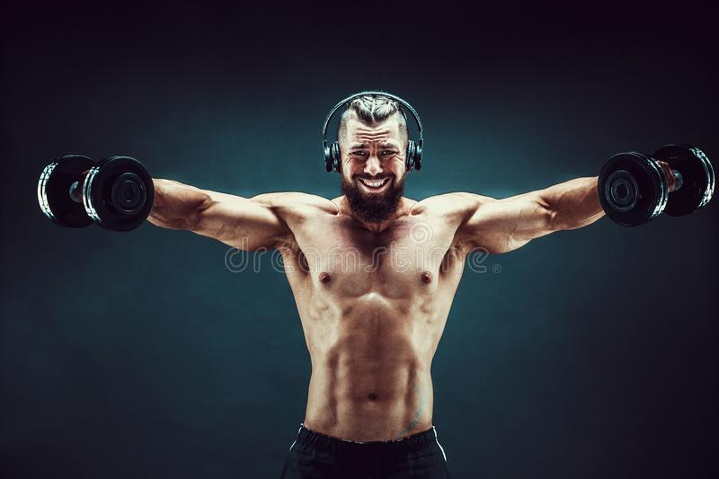 Man training muscles with dumbbells in studio on dark background. stock photo