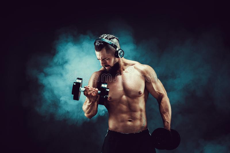 Man training muscles with dumbbells in studio on dark background with smoke. Athletic man training muscles with dumbbells in studio on dark background with royalty free stock photos