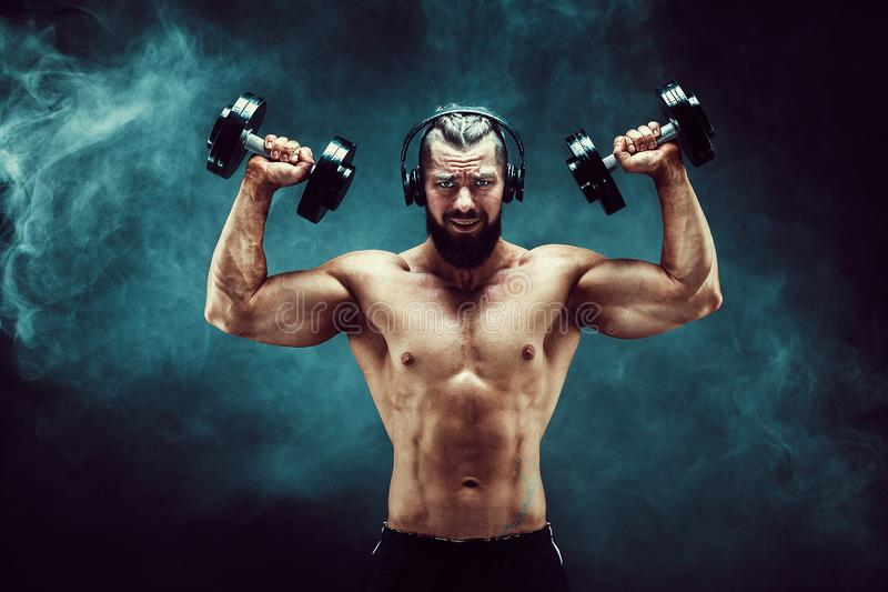 Man training muscles with dumbbells in studio on dark background with smoke. royalty free stock image