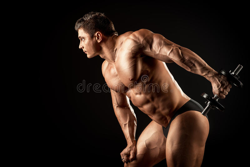 Man training. Portrait of a handsome muscular bodybuilder posing with dumbbells over black background stock photo