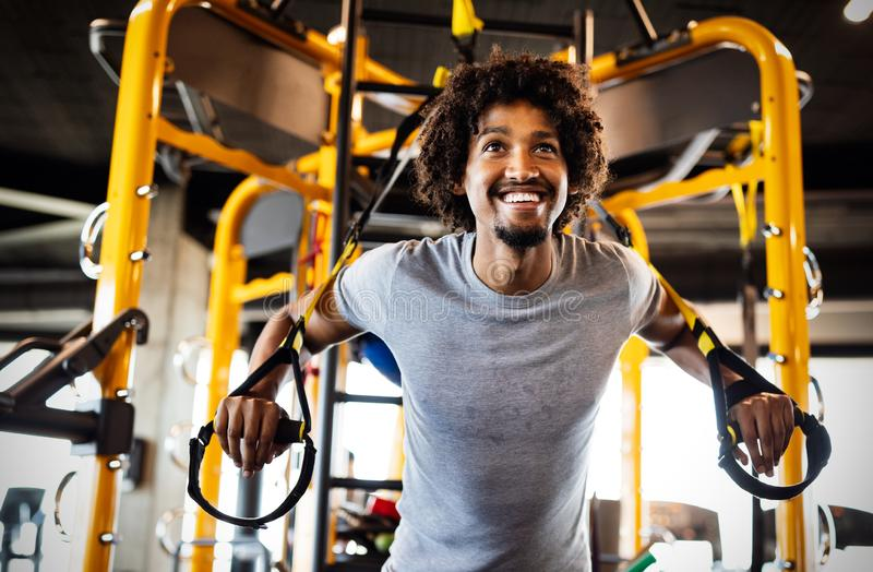 Man training with trx fitness straps in the gym. Workout healthy lifestyle sport concept. Man doing push ups training with trx fitness straps in the gym. Workout stock photo