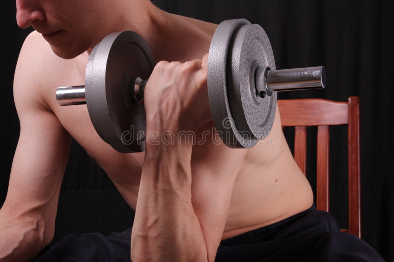 Man training with weight. In dramatic studio light stock photo
