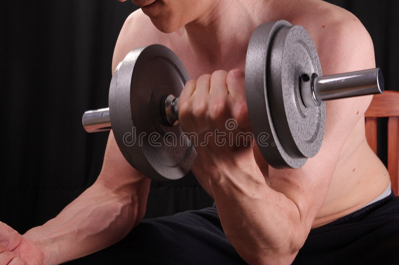 Man training with weight. In dramatic studio light stock photos