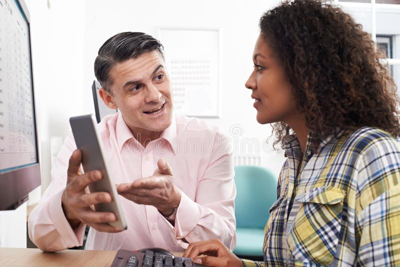 Man Training Woman In Office Using Digital Tablet stock photography