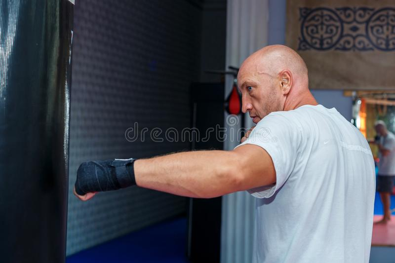 A man trains at the MMA bag to work out the bumps royalty free stock photo