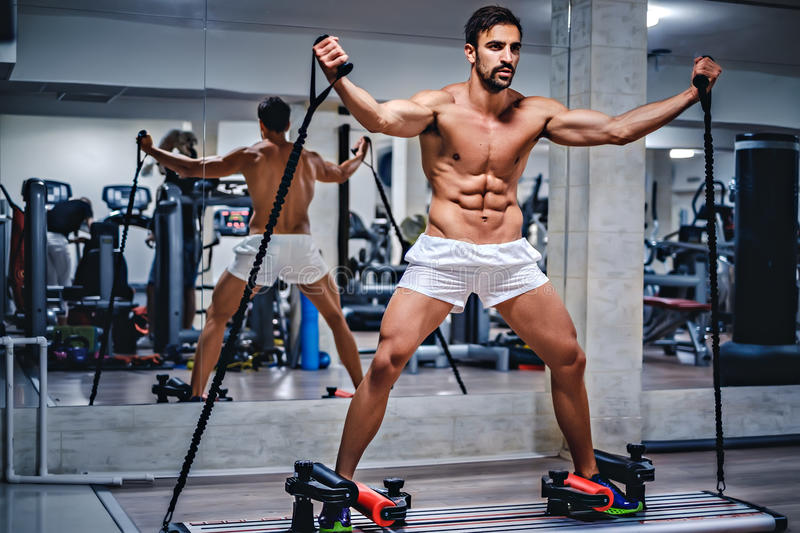 Man trains on slider. In the gym royalty free stock images