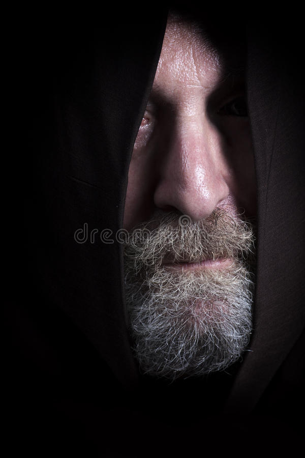 Man tramp with sackcloth and beard, face partially hidden. A man tramp has his head covered by a robe. From the hood is facing the beard, the nose and the royalty free stock image