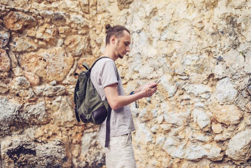 Man traveler with backpack looking at his smartphone on the background of a stone wall stock photography